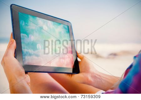 Woman sitting on beach in deck chair using tablet pc showing digitally generated pink and blue girly design poster