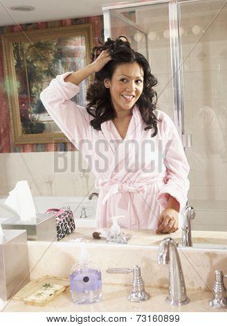 Hispanic woman looking in bathroom mirror