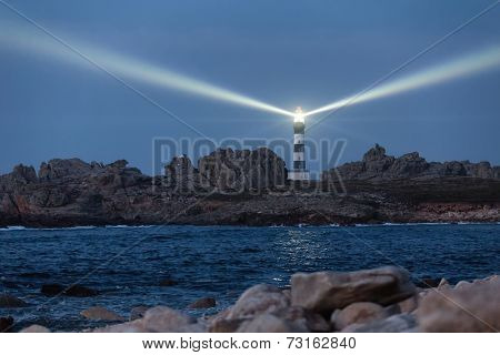 Powerful lighted lighthouse at dusk, Creach point, Ushant island, France