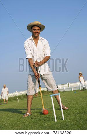 Hispanic man playing croquet