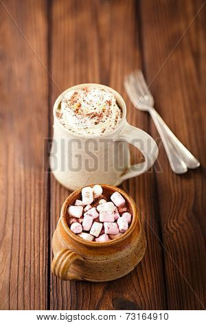 hot chocolat vintage mugs, topping with marshmallow, cream and grated chocolate on textured wood