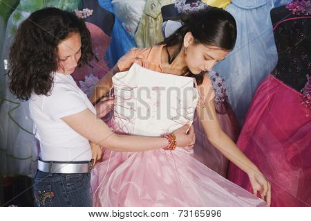 Hispanic girl trying on Quinceanera dress