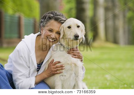 African American woman hugging dog