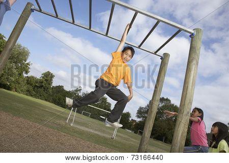 Asian boy hanging on jungle gym