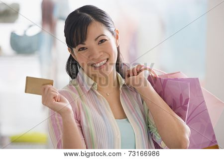 Chinese woman holding shopping bags and credit card