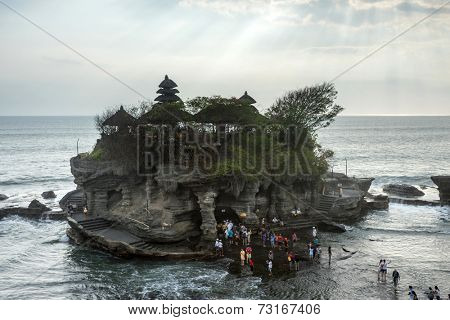 SEPTEMBER 17, 2014, BALI, INDONESIA: Tourists and devotees throng the Tanah Lot Temple. The ancient Hindu temple built on a rock on the shore is a famous tourist attraction on Bali Island.