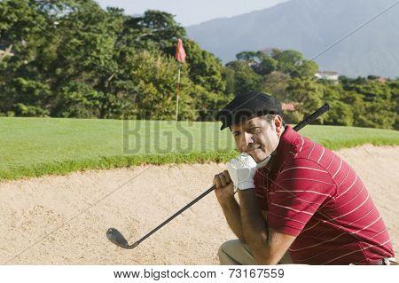 Hispanic man in golf course sand trap