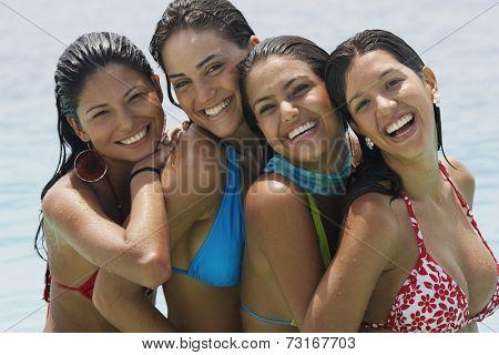 South American women hugging at beach