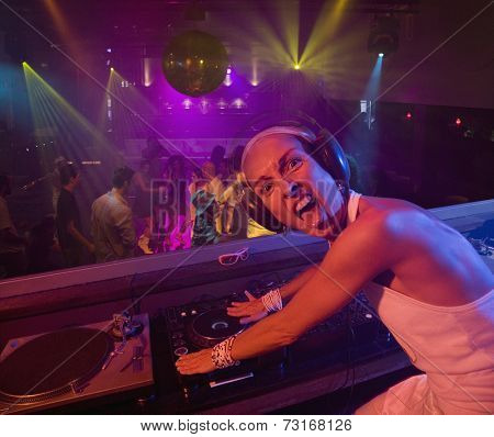 Hispanic woman djing at nightclub