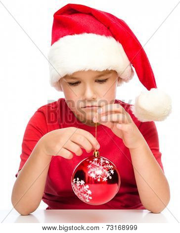 Young unhappy girl in santa cloth is holding a christmas decoration, isolated over white