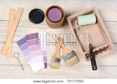 High angle shot of equipment laid out in preparation to paint. Items include: an open paint can, paint, roller, brushes, chip chart, stirrers, opener and tray.