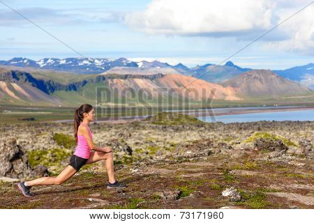 Fitness girl doing lunges exercise in nature. Female sport model exercising doing front forward lunge training legs and glute outside in beautiful landscape on Iceland.