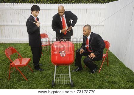 Multi-ethnic businessmen looking at barbeque