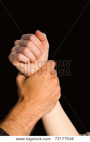 Womans wrist held by man on black background