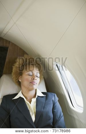 African American businesswoman sleeping on airplane