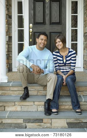 Hispanic father and daughter sitting on porch steps
