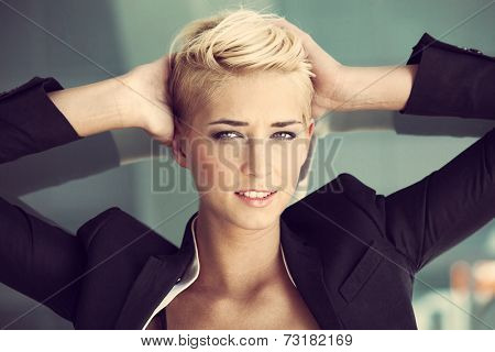 smiling young blue eyes woman with trendy short blonde hair  outdoor portrait recline on glass window hands in hair