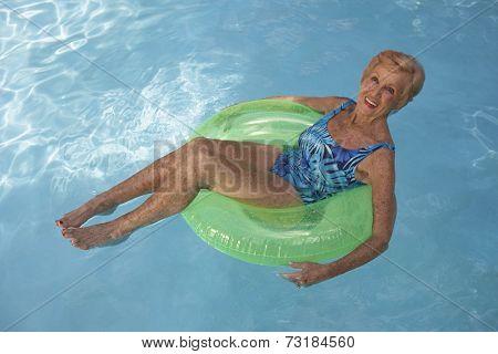 Senior woman floating in swimming pool