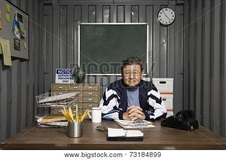 Senior Asian male worker at desk