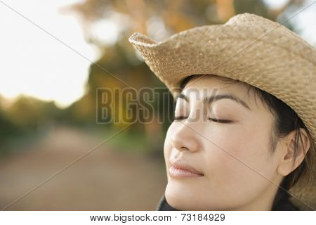 Asian woman wearing cowboy hat