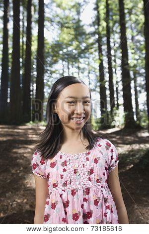 Asian girl standing in woods