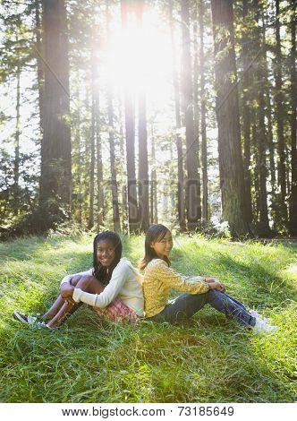 Multi-ethnic girls sitting in woods