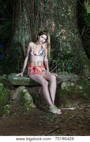 Hispanic woman wearing bikini in woods