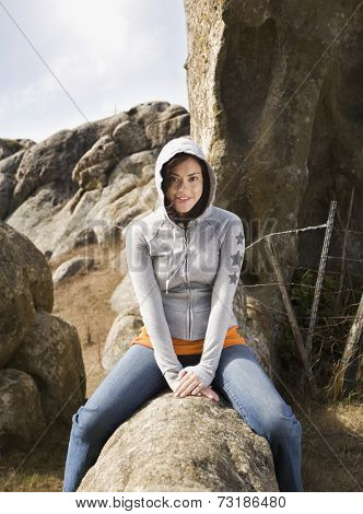 Hispanic woman sitting on rock formation