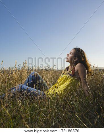 Hispanic woman sitting in field