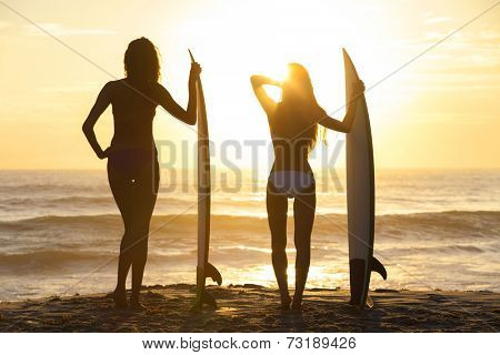 Rear view silhouettes of beautiful sexy young women surfer girls in bikinis with surfboards on a beach at sunset or sunrise