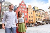Couple in Stockholm, Sweden, Europe. Happy multiracial young couple walking outside on Stortorget big square in Gamla Stan, the old town of Stockholm. Scandinavian man, Asian woman. poster