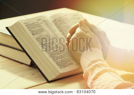 Hands of old woman with Bible on table