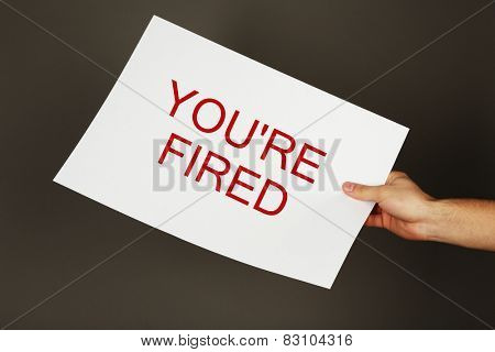 Sheet of paper with text You're Fired in male hand on dark background