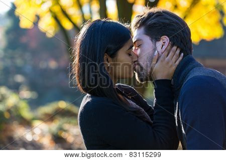 Couple Kissing In Front Of Autumn Tree