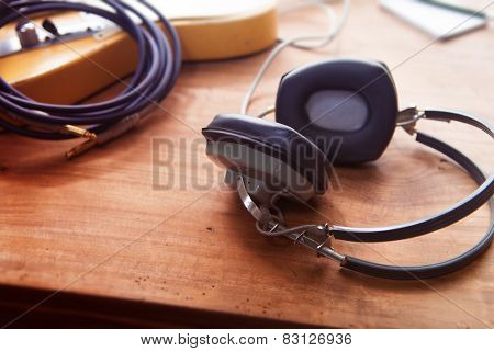 Music Recording scene. Professional grade headphones on a rustic or bare wooden table, with by-the-window type warm light. An electric guitar, memo pad , in the background. Shallow depth of field.