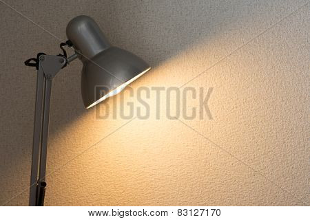 Silver desk lamp or arm lamp in front of a white wall with incandescent type light bulb illuminating the wall.