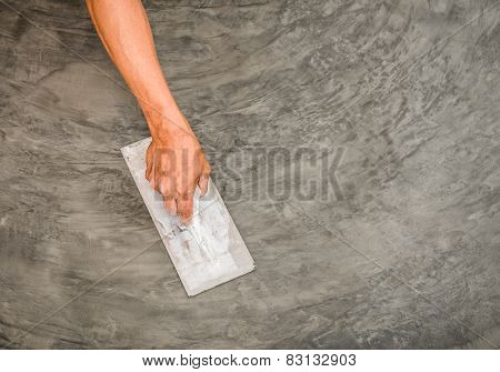 Hand Using Steel Trowel To Finish Polished Wet Concrete Surface
