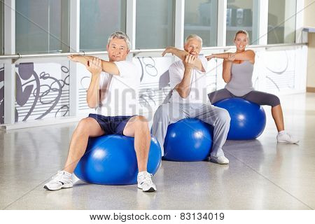 Group of senior people stretching in gym and sitting on exercise balls