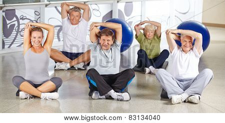 Senior group stretching in fitness center before doing back training