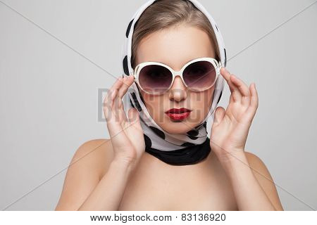 Stylish woman posing in sunglasses and scarf on head