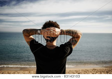 Caucasian Boy On Beach Standing In Sand With Hands Behind Head And Looking At Ocean Enjoying Sun And