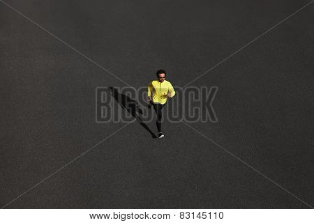 Top View Runner Man Running Sprinting For Success On Run At Black Road In Yellow Sportswear. Muscula