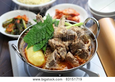 gamjatang, pork bone and potato soup, korean cuisine, simmering on the portable gas stove