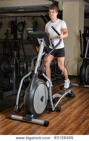 Man's Workout On Elliptical Machine