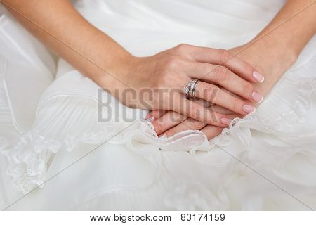 bride's Hand with Diamond ring on white dress