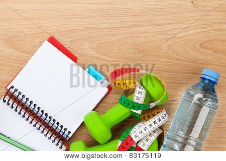 Dumbells, tape measure, water bottle and notepad for copy space. Fitness and health