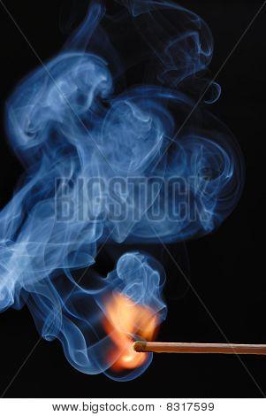 Macro of burning match and smoke on black background poster