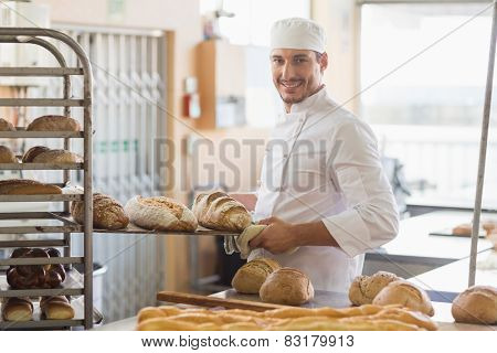 Smiling baker holding tray of bread in the kitchen of the bakery