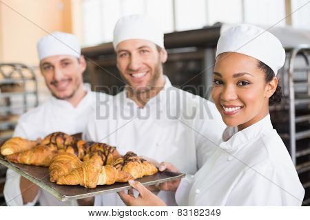 Team of bakers smiling at camera with trays of croissants in the kitchen of the bakery poster
