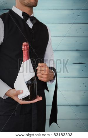Waiter holding magnum of champagne against wooden planks